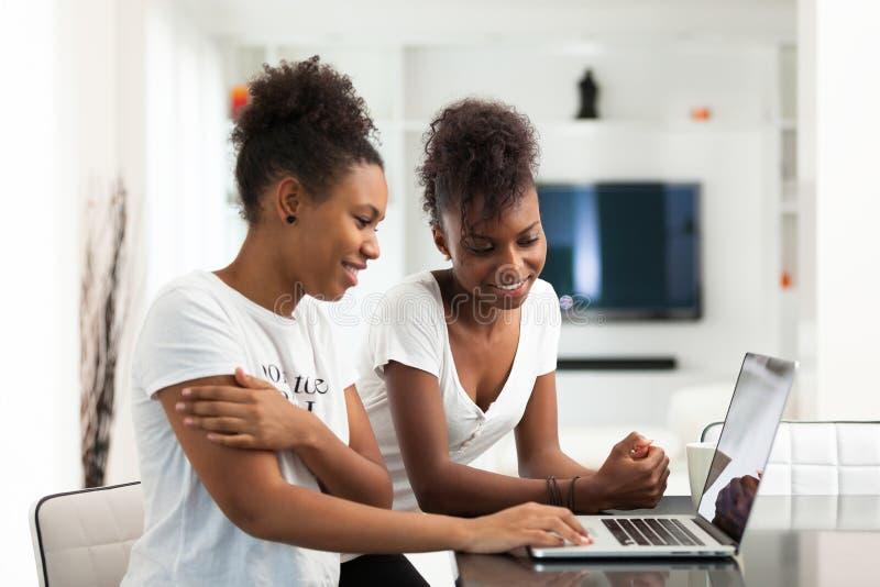 Filles d'étudiant d'afro-américain à l'aide d'un ordinateur portable - p noir photographie stock libre de droits