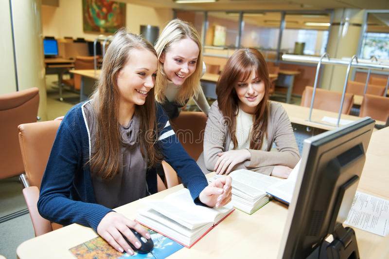 Filles d'étudiant travaillant avec l'ordinateur dans la bibliothèque photographie stock