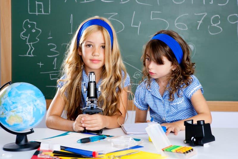 Filles d'enfants à la salle de classe d'école avec le microscope image libre de droits