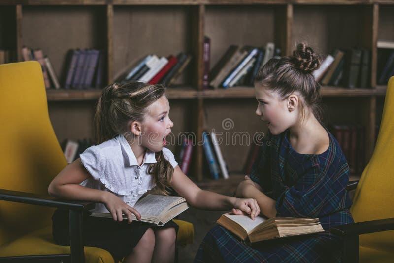 Filles d'enfants dans la bibliothèque avec des livres dans l'éducation image libre de droits
