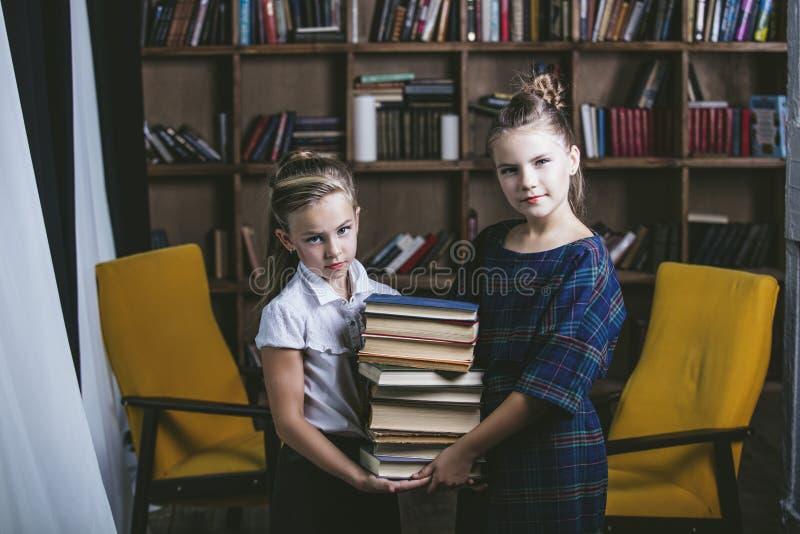 Filles d'enfants dans la bibliothèque avec des livres dans l'éducation photographie stock