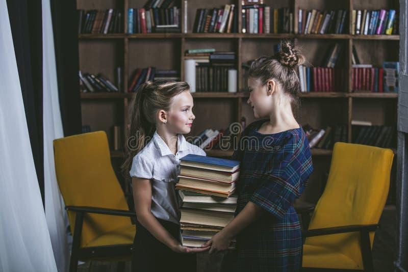 Filles d'enfants dans la bibliothèque avec des livres dans l'éducation photo libre de droits