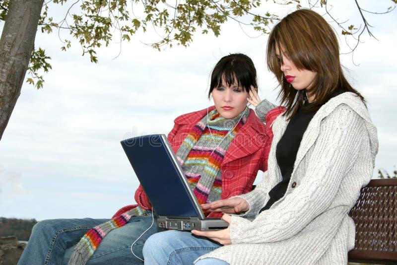 Filles d'université à l'extérieur avec l'ordinateur portatif photo libre de droits
