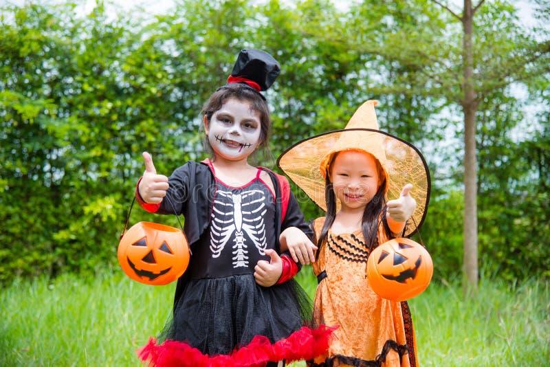 Filles dans la position de costume de Halloween en parc photographie stock
