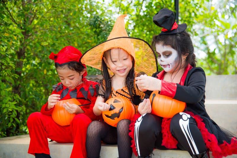 Filles dans le costume de Halloween se reposant sur l'escalier et le sourire images stock