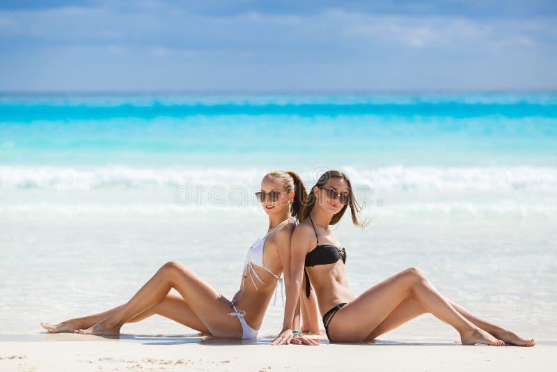 Filles dans prendre un bain de soleil de bikinis, se reposant sur la plage photographie stock