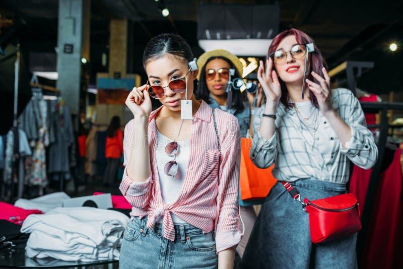 Filles de hippie choisissant des vêtements dans la boutique, concept de filles d'achats de mode photo stock