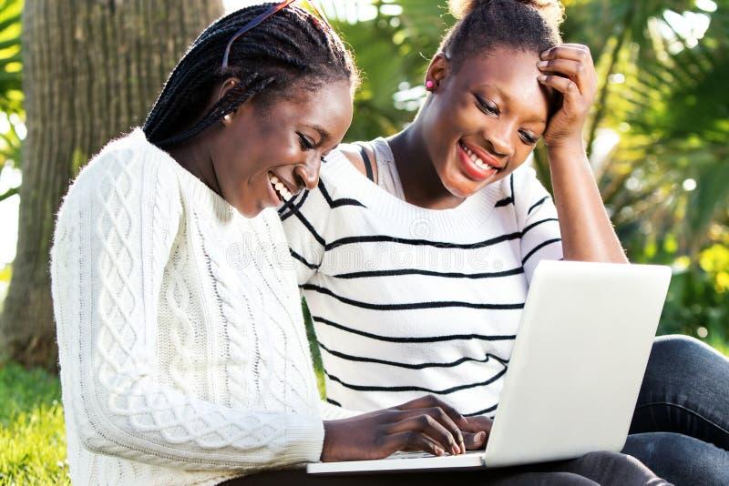 Filles de l'adolescence africaines ayant l'amusement sur l'ordinateur portable dans le parc images libres de droits
