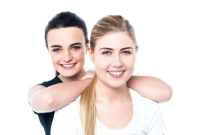 Filles de l'adolescence de sourire attirantes faisant face à l'appareil-photo photographie stock