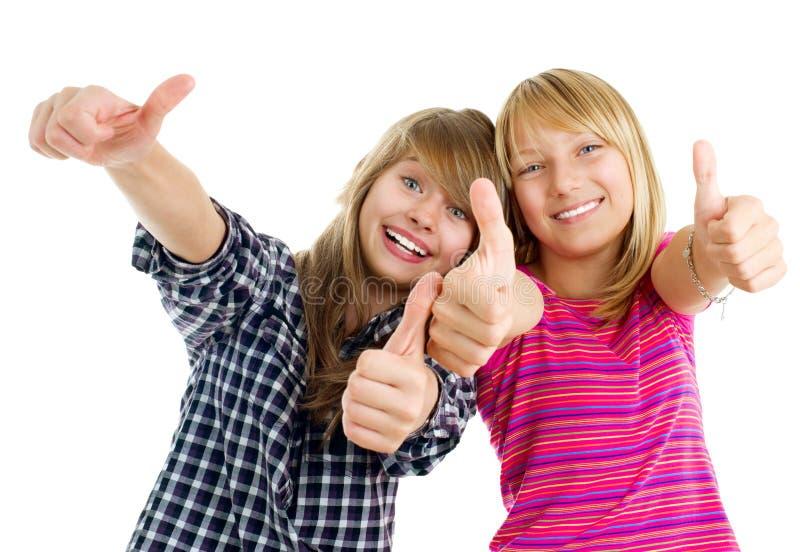 Filles de l'adolescence heureuses affichant des pouces vers le haut photographie stock