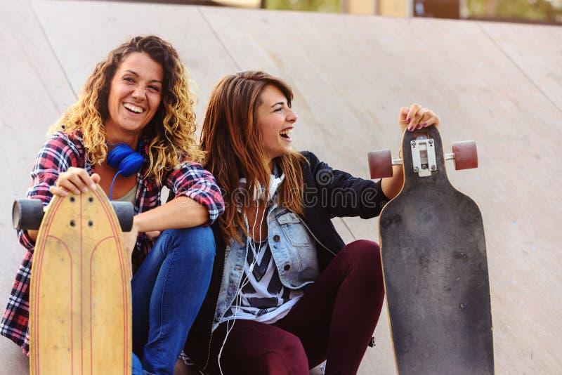 Filles de patin s'asseyant dans la rue traînant image stock