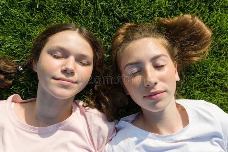 Filles de sourire avec les yeux fermés se trouvant sur l'herbe verte images stock