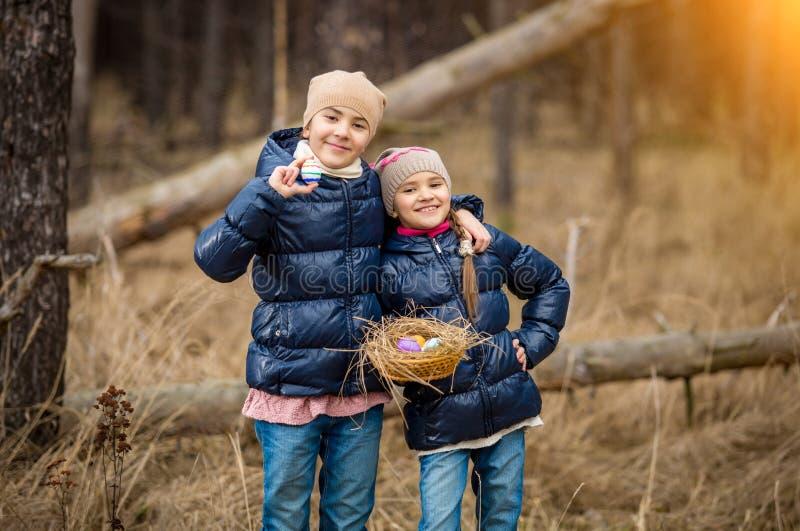 Filles de sourire posant avec le panier plein des oeufs de pâques à la forêt images stock
