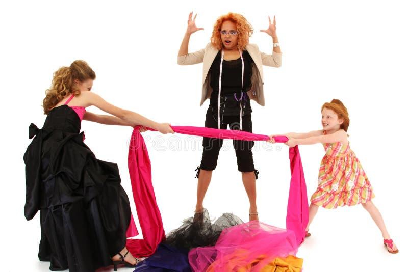 Filles de spectacle pompeux combattant au-dessus du créateur de robe photographie stock libre de droits