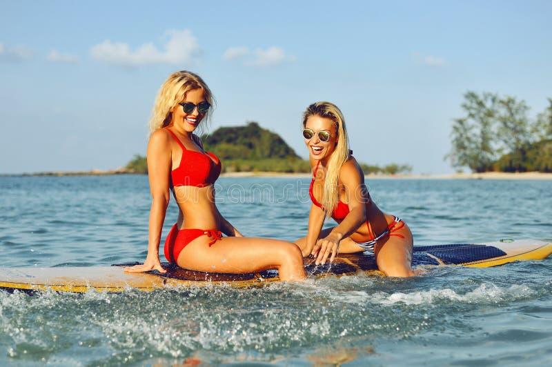 Filles de surfer ayant l'amusement sur une planche de surf en mer photo libre de droits