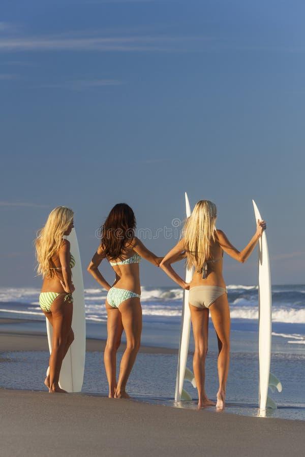 Filles de surfer de femmes dans des bikinis avec des planches de surf à la plage images libres de droits