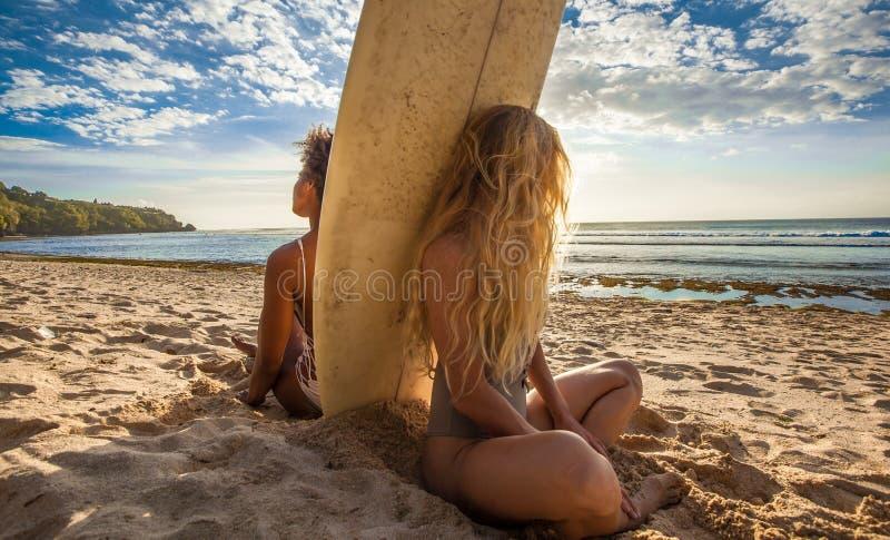 Filles de surfer de métis s'asseyant de nouveau au dos avec la planche de surf dans l'intervalle images stock