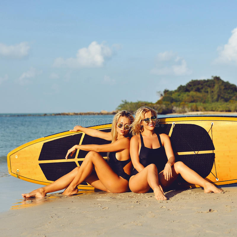Filles de surfer posant avec la planche de surf sur une plage photographie stock libre de droits