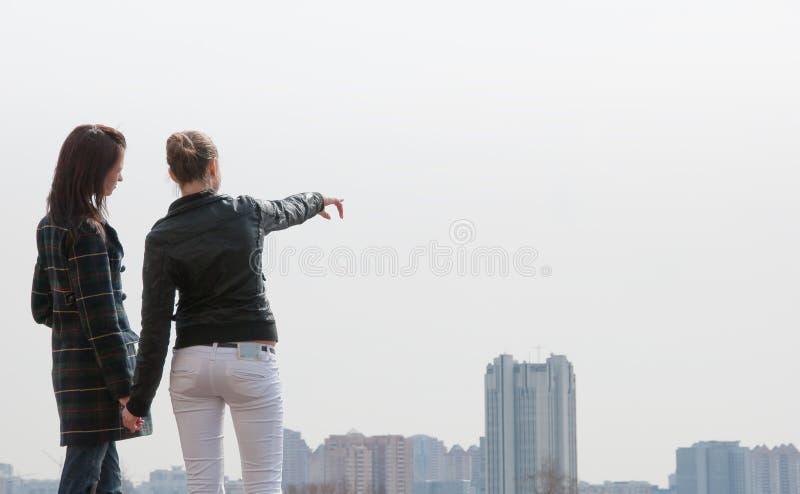 filles de ville regardant le panorama à deux images stock