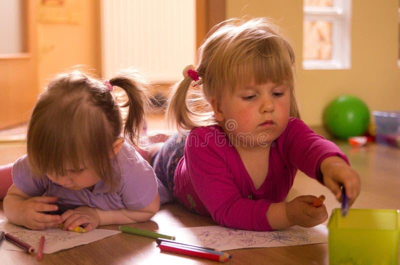 Filles dessinant sur le plancher photographie stock