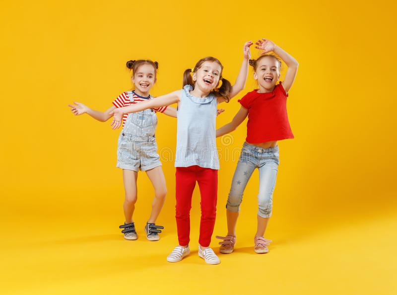 Filles drôles d'enfants sautant sur le fond jaune coloré photo stock