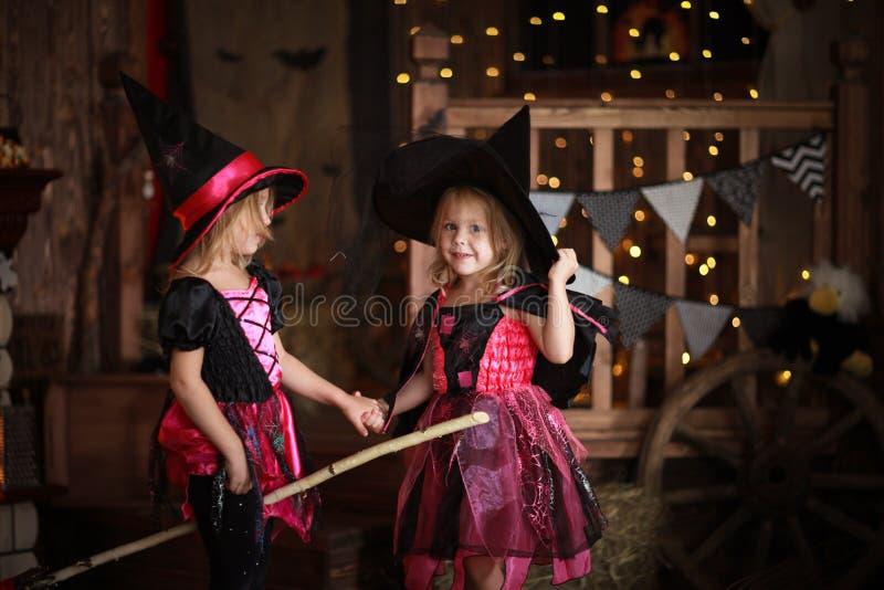 Filles drôles d'enfants dans le costume de sorcière pour le backg d'obscurité de Halloween photos stock