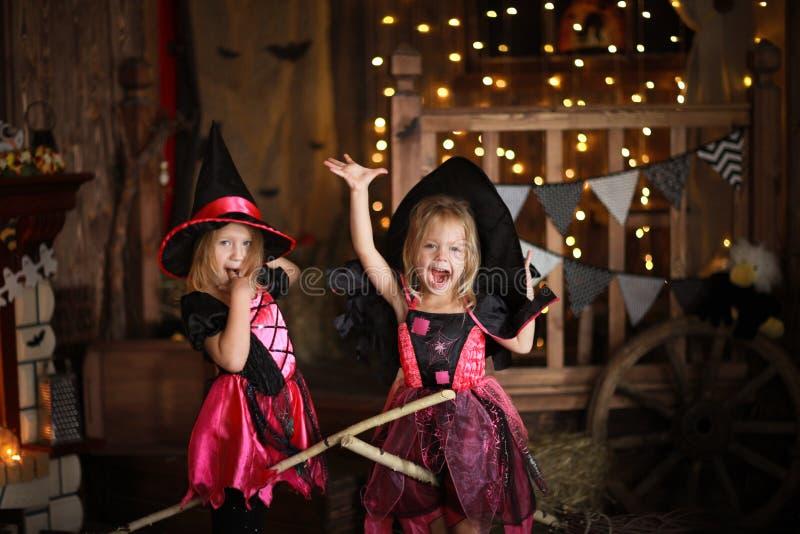 Filles drôles d'enfants dans le costume de sorcière pour le backg d'obscurité de Halloween photographie stock libre de droits