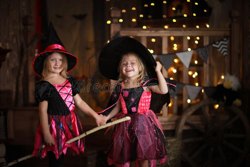 Filles drôles d'enfants dans le costume de sorcière pour le backg d'obscurité de Halloween image libre de droits