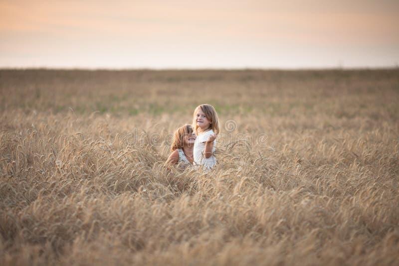 Filles drôles jouant avec du seigle au coucher du soleil, mode de vie photographie stock