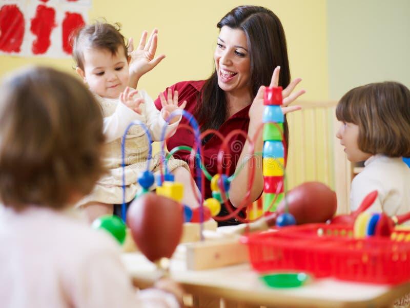 Filles et professeur féminin dans le jardin d'enfants photos stock