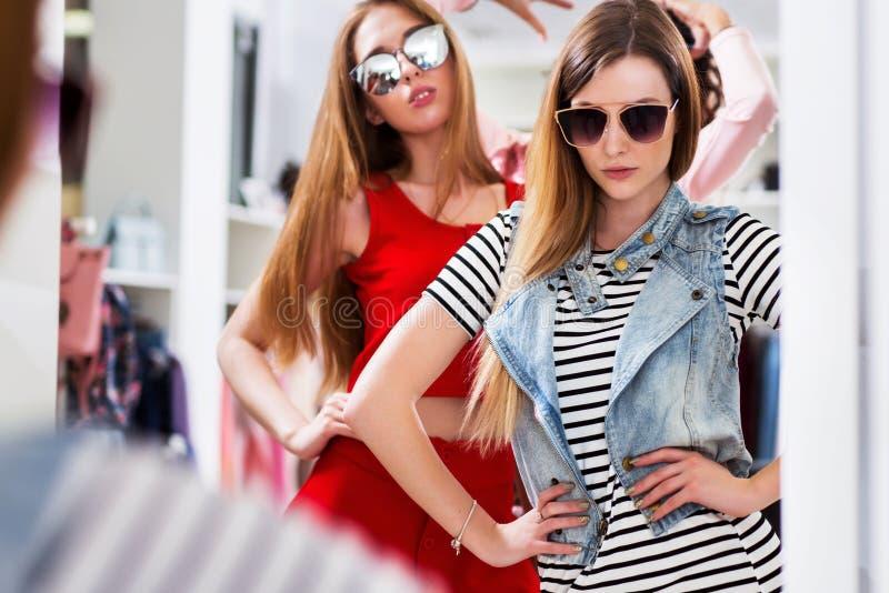 Filles fascinantes essayant sur des lunettes de soleil posant devant le miroir dans la boutique de mode photo libre de droits