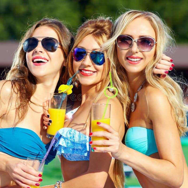 Filles heureuses avec des boissons sur la partie d'été photo stock