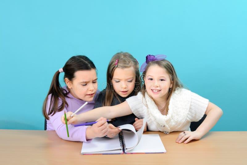 Filles heureuses d'école effectuant leur travail dans la salle de classe image stock
