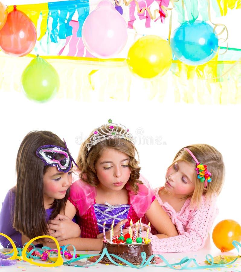 Filles heureuses d'enfants soufflant le gâteau de fête d'anniversaire photographie stock