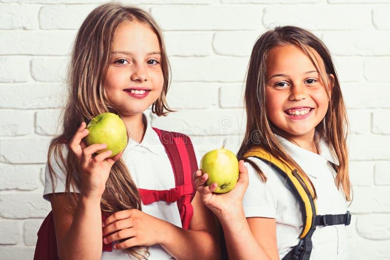 Filles heureuses mangeant la pomme verte fraîche à l'école images libres de droits