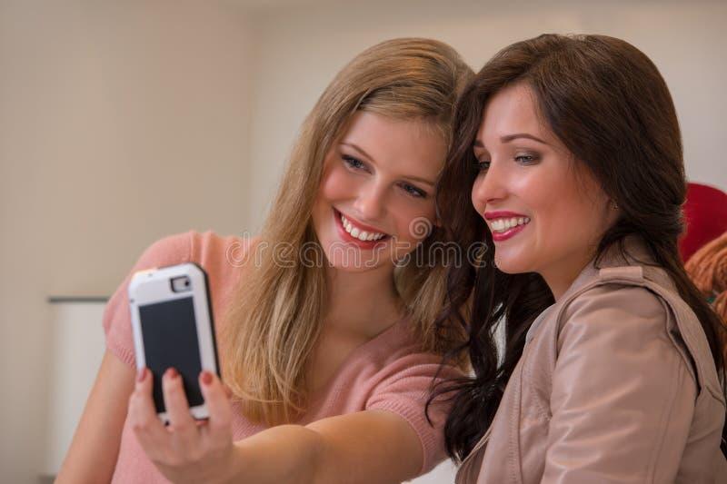 Filles heureuses photographiant à l'intérieur le selfie tout en faisant des emplettes image stock