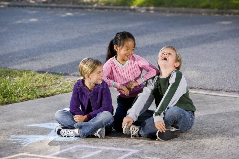 Filles incitant le garçon à rire photo stock