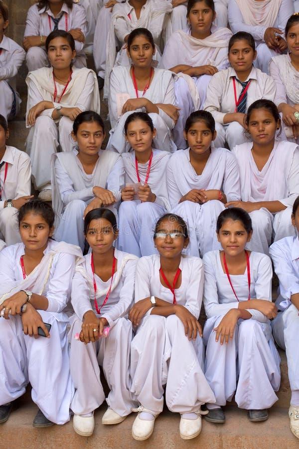 Filles indiennes d'école s'asseyant chez Qutub Minar, Delhi, Inde image stock