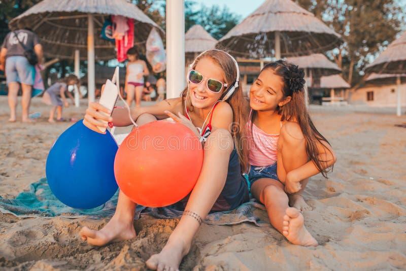 Filles jouant avec des téléphones portables sur la plage sablonneuse photographie stock libre de droits