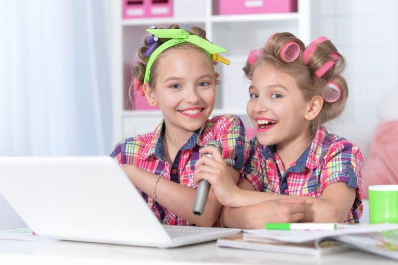 Filles jumelles mignonnes dans des bigoudis de cheveux chantant le karaoke avec l'ordinateur portable photographie stock libre de droits
