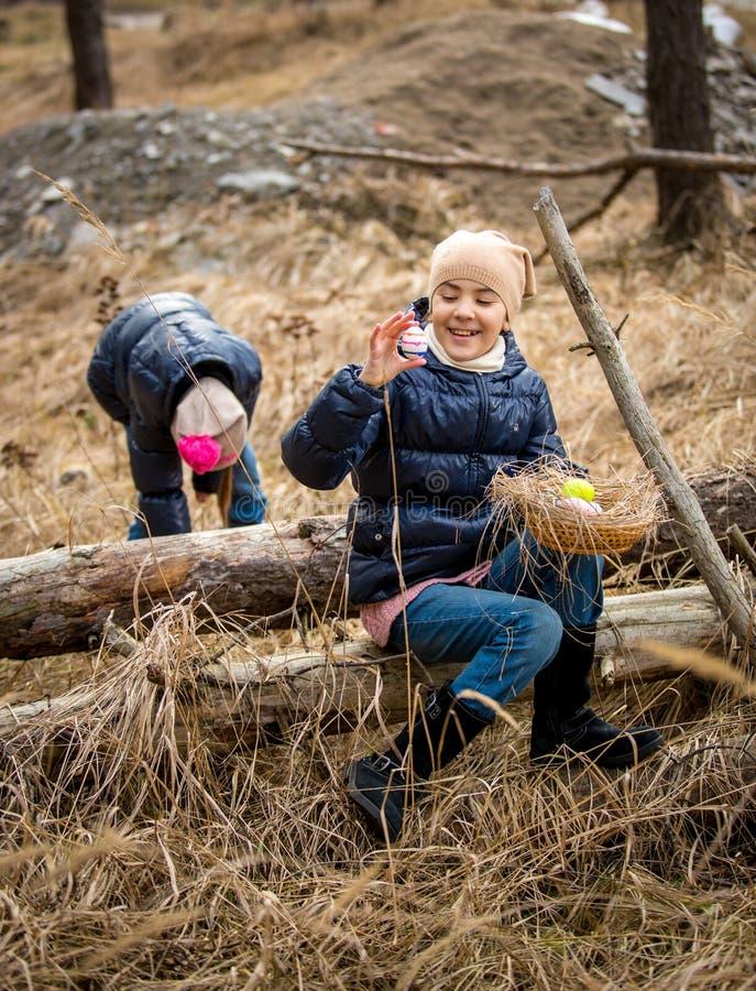 Filles mignonnes ayant la chasse à oeuf de pâques à la forêt au jour froid d'avril photographie stock