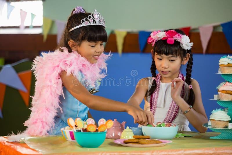 Filles mignonnes ayant la confiserie pendant la fête d'anniversaire photo libre de droits
