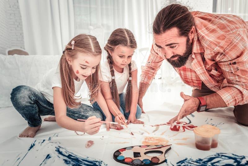Filles mignonnes et leur dessin de papa dans la chambre à coucher légère images stock