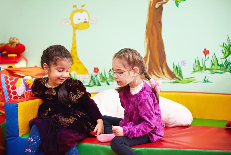 Filles mignonnes parlant et jouant dans le jardin d'enfants pour des enfants avec les besoins spéciaux images libres de droits
