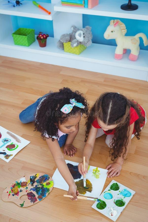 Filles mignonnes peignant la pose sur le plancher photo libre de droits