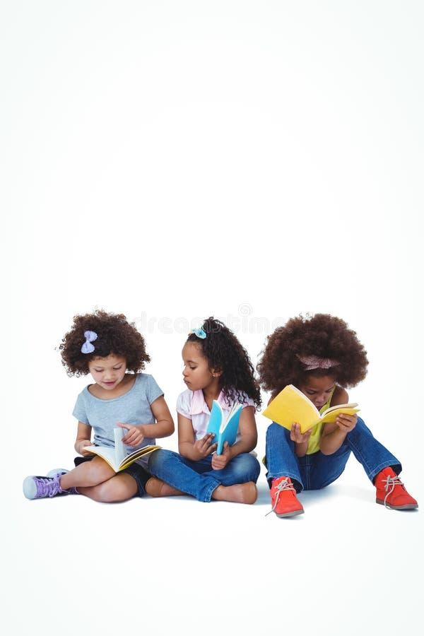 Filles mignonnes s'asseyant sur des livres de lecture de plancher images libres de droits