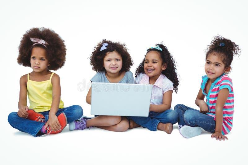 Filles mignonnes s'asseyant sur le plancher utilisant l'ordinateur portable photos libres de droits