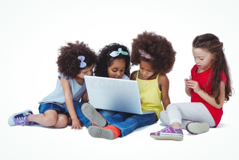 Filles mignonnes s'asseyant sur le plancher utilisant l'ordinateur portable photos stock