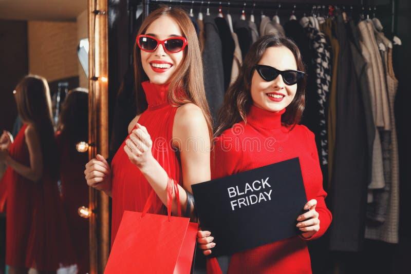Filles réussies tenant la carte de Black Friday photos libres de droits