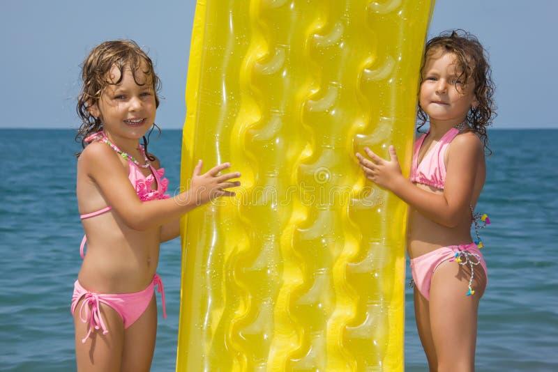 Filles restant sur la plage avec le matelas gonflable images libres de droits